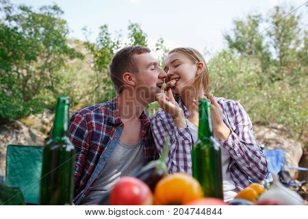 Group of friends having picnic in a park on a sunny day People hanging out, having fun while grilling and relaxing. Cheerful friends on picnic in the park. Group Of People Dining Togetherness Concept