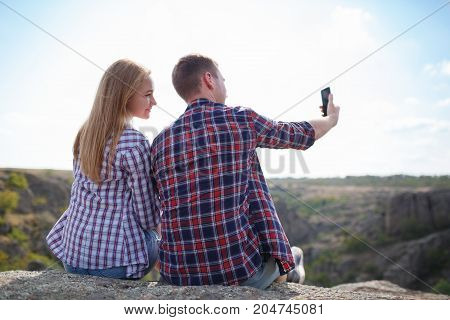 couple of hikers taking a selfie. Tourists woman and man in mountains make selfie uses mobile phone. Mountain selfie in summer. Healthy lifestyle, adventure, tourism, hiking and technology concept.