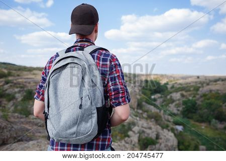 The guy is standing on the mountain and enjoying the beautiful view. A traveler with a backpack makes a photo of the mountains. Photographer with camera on top of the mountain. Beautiful mountain view