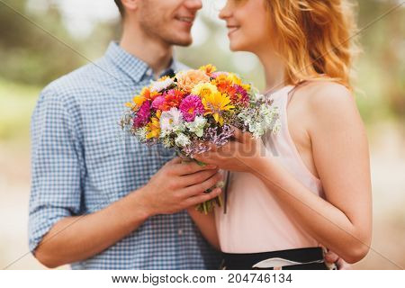 The guy gave his girl beautiful autumn flowers standing in the woods. A young couple are walking in a coniferous forest. Coniferous forest in the background. Background blur. Great time for a walk