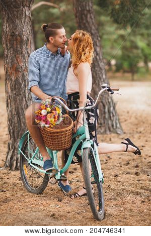 Happy young couple walking in the woods with a bicycle. Healthy lifestyle