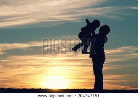 a mother with her child embracing at sunset.