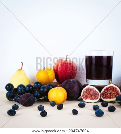 Glass of dark grape juice with organic autumn seasonal fruits. Diet and healthy food concept.