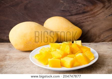 Sliced mango fruit on white dish and wooden background