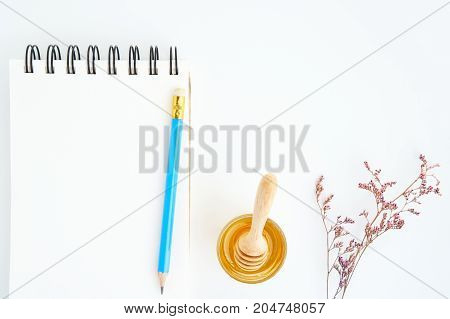 Blank book with pencil Put on a white table with honey and flowers Used to take notes about a person's health.