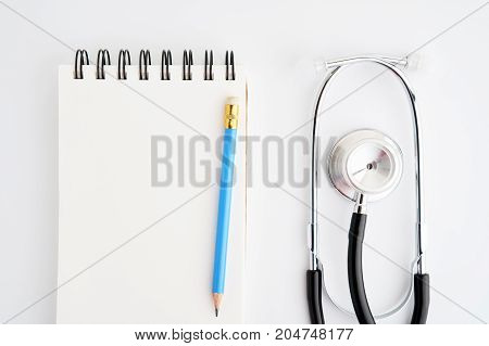 Blank notebook with pencil put on white desk with stethoscope. Used to take notes about a person's health.