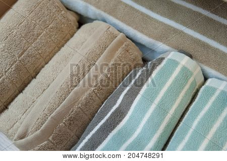 Different colors of towel in front of the cotton print background Bath towels of different colors in shelf on light background
