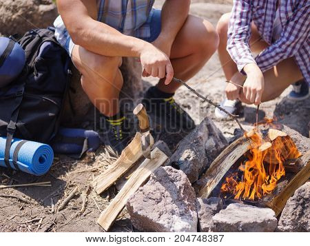 A sweet girl helps her boyfriend to kindle a fire on the nature. A young couple is preparing to grill meat on the grill. Healthy lifestyle.