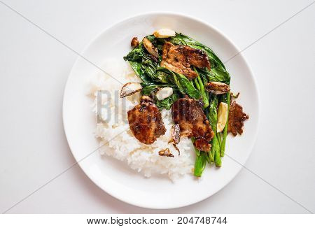 Thai food,stir fried Chinese kale  with pork and cooked rice on dish ready to eating