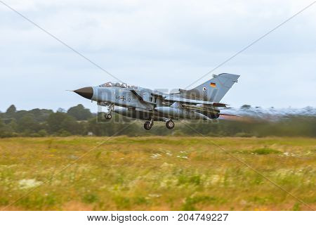 Schleswig - Jagel Germany - June 19 2014: Germany - Air Force Panavia Tornado board number 4632 is takeoff for background of field and skyline the airbase during NATO Tiger Meet 2014