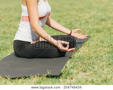 Close-up image of body parts girl's meditation at the health club outside with personal trainer, learning the correct form.