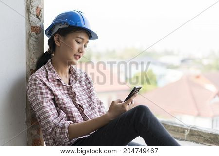 The asian woman engineer who use mobile phone in construction building at breaking time