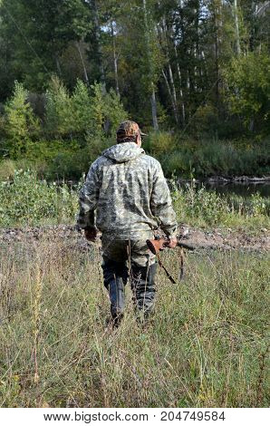 the going hunter with a gun in a hand, a hunter in a camouflage suit
