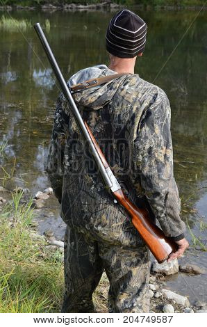 the hunter with a gun is situated on the bank of the river, the hunter with a gun on a shoulder