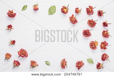 Dried roses flowers on vintage rustic white wooden desk as background.Top view. Concept of love and romantic and passing of time