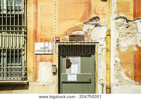 PRATI ITALY - JUNE 26 2016: An old and teared orange wall of the Archaeological Museum with a yellow vertical pipe and a window with bars in a sunny day. Prati Italy.