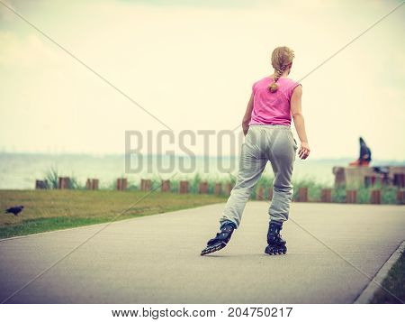 Holidays active lifestyle freedom concept. Young fit woman on roller skates riding outdoors on sea coast girl on sunny day
