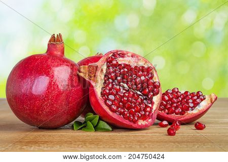 pomegranates whole and cut on wooden table against natural background