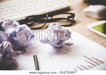 Business workplace with keyboard mouse and crumpled paper balls papers with graphs and diagrams . Business Concept