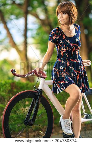 woman with bicycle in the garden. Girl on bike concept