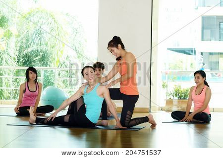 Group of asian women and man practicing yoga fitness stretching flexibility pose working out healthy lifestyle wellness well being