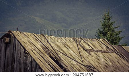Vintage faded image of an old wooden barn roof falling apart dew to lack of maintenance a mountain farm