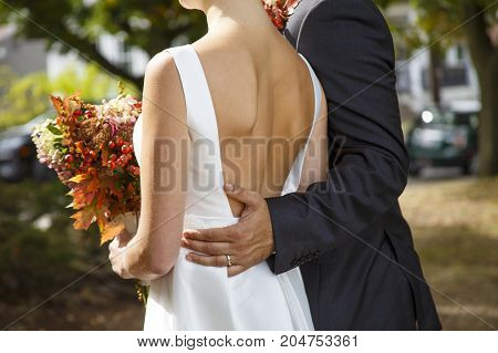 groom and bride with autumn bouquet outdoors. closeup of a married couple. Goose bumps and shivers at the bride. the bride in a wedding dress with a deep neckline at the back