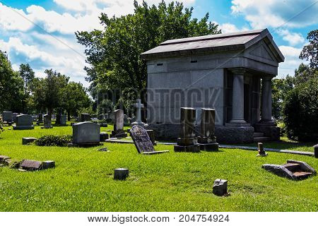 Mausoleum in a graveyard with scattered headstones.