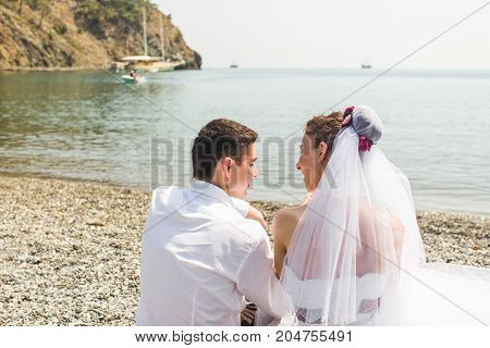 Young love couple sitting together on beach.
