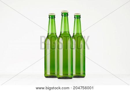 Group green longneck beer bottles 500ml mock up. Template for advertising design branding identity on white wood table.