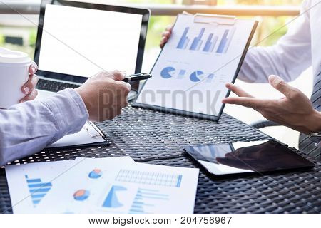 Business people discuss together about there work by graph document and setting in outdoor for planning financial strategy