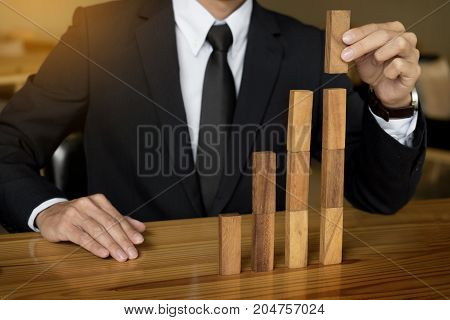 Concept growing value. hand of businessman pick up a wood block like bar graph growth