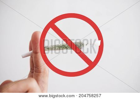 Hand holding rolled joint cigarette with not allow sign