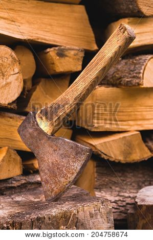 The ax is stuck in a log against the backdrop of chopped firewood lying in a flat pile. Close-up