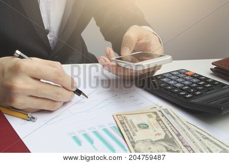 Hand use smartphone and calculator on the office desk investment and property for concept.