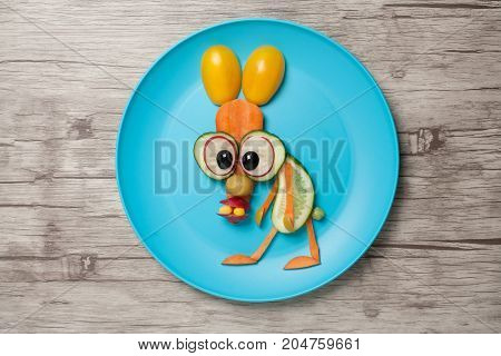 Surprised vegetable hare on plate and wooden background