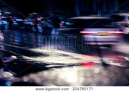 Night Traffic In City. Blurred Cars Driving On Wet Road During Heavy Rain.