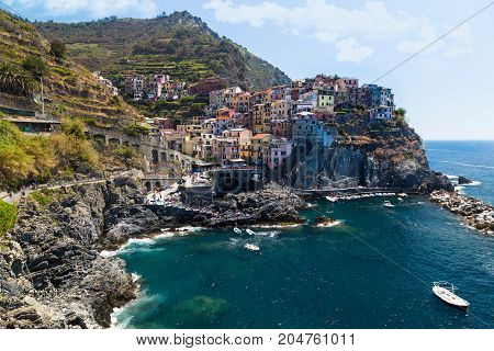View of the colorful houses of ancient city Manarola and the coast Italy. Cinque Terre National Park Ligurian Riviera UNESCO World Heritage Site. Tourist sight. Between the mountains and the sea
