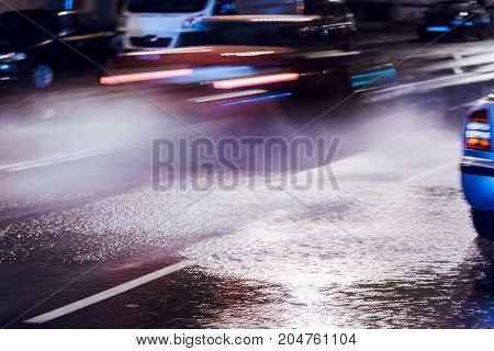 Blurred Cars Driving During Heavy Rain And Splashing Water From The Wheels. City Traffic At Night.