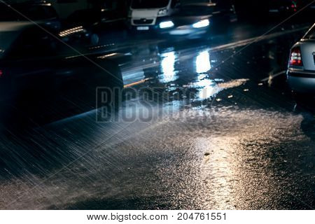 Blurred Cars With Bright Headlights On Rainy Road At Night