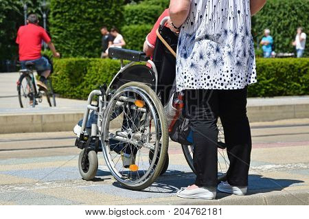 Man in wheelchair waits for tram on the street