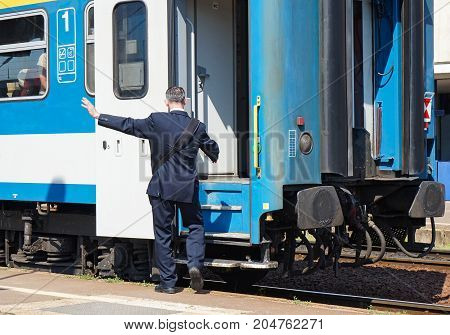 Train conductor at the station next to a train