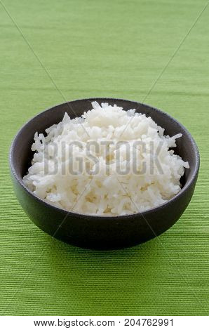 Rice In The Black Bowl On Green Table Background