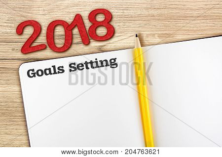 Top view of 2018 new year red number and goals setting with blank open notebook and yellow pencil on wooden table topMock up for adding your content or design