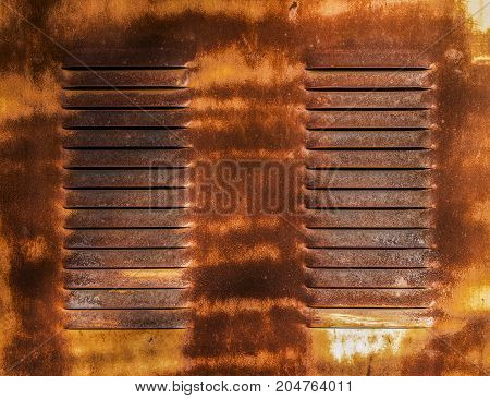 Old rusty metal door with ventilation holes. Grunge metal background