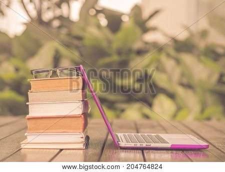 Vintage style stack of books with laptop on wood table outdoor.