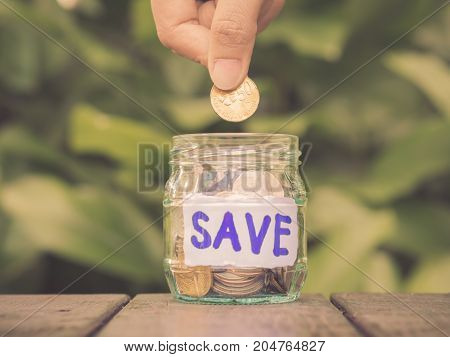 Retro abstract money saving hand put coin to glass jar coins on wood table with green tree background.