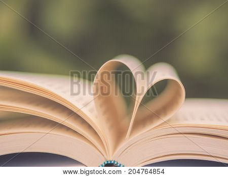 Retro book on table in garden with top one opened and pages forming heart shape with selective focus.