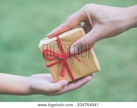 Close up of child and mother hands with gift box over green background. Holidays present christmas childhood and happiness concept .