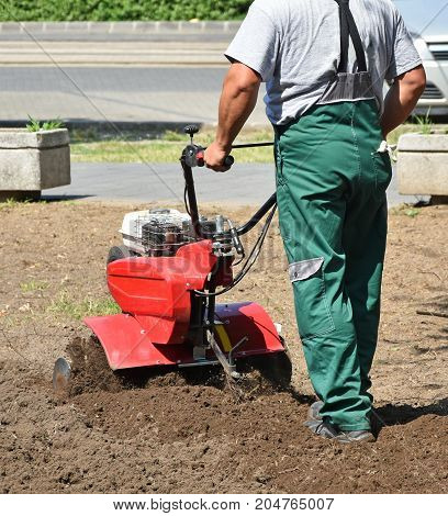 Gardener works with a tiller machinery in the park
